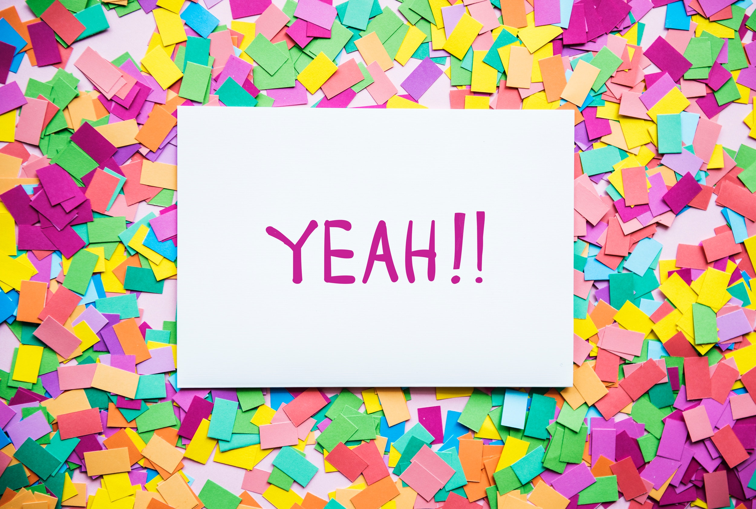 "Card with the word ""yeah"" on top of confetti"