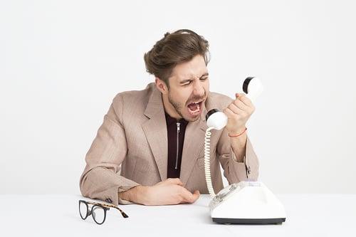 man-wearing-brown-suit-jacket-mocking-on-white-telephone-1587014